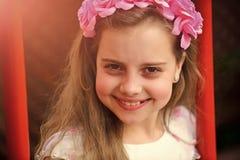 Счастливый ребенк имея потеху Маленькая девочка с цветком в волосах, детстве и счастье Стоковое фото RF
