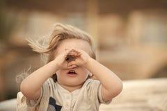 Счастливый ребенк имея потеху Малый мальчик ребенка при серьезная сторона держа руки близко наблюдает стоковое фото