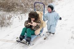 Счастливый ребенок в моде зимы одевает представлять с свиньей игрушки в дворе его дома в деревне Первый снег, семья, традиция Стоковое Изображение
