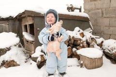 Счастливый ребенок в моде зимы одевает представлять с свиньей игрушки в дворе его дома в деревне Первый снег, семья, традиция Стоковое Изображение RF