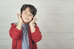 Счастливый ребенок в наушниках стоковые фотографии rf