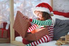 Счастливый ребенок в пижамах с подарками рождества стоковые изображения rf