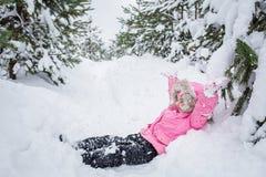 Счастливый ребенок в ребенке соснового леса зимы в розовой куртке бросает снег на открытом воздухе стоковое изображение
