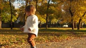 Счастливый ребенок играя в парке Маленький младенец бежать вокруг парка осени, смеясь и играя с листьями осени акции видеоматериалы