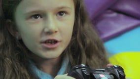 Счастливый ребенок играя игру консоли, время расточительствуя, наркоманию игры сток-видео