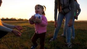 Счастливый ребенок играя шарик с мамой и сестрами Семья играя с небольшим ребенком шариком детей в парке на заходе солнца видеоматериал