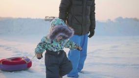 Счастливый ребенок идет через снег с его отцом Ландшафт зимы Snowy Спорт outdoors видеоматериал