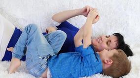 Счастливый ребенок и его игра мамы с их руками, лежа на белой софе видеоматериал