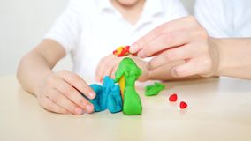 Счастливый ребенок и его игра мамы с пластилином или тестом для работы видеоматериал