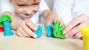Счастливый ребенок и мать играя с моделью смешивая, пластилином, тесто акции видеоматериалы