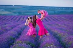Счастливый ребенок матери и дочери вместе с желтыми цветками одуванчика в летнем дне наслаждается свободным временем каникул совм стоковое фото rf