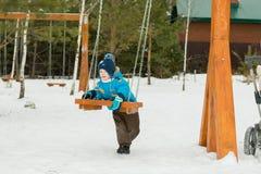 Счастливый ребенок на качаниях на парке зимы Стоковая Фотография RF