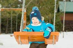 Счастливый ребенок на качаниях на парке зимы Стоковое Фото
