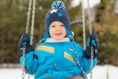 Счастливый ребенок на качаниях на парке зимы Стоковое Изображение