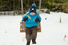 Счастливый ребенок на качаниях на парке зимы Стоковые Изображения