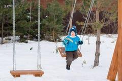 Счастливый ребенок на качаниях на парке зимы Стоковые Фото