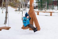Счастливый ребенок на качаниях на парке зимы Стоковое фото RF