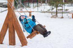 Счастливый ребенок на качаниях на парке зимы Стоковые Фотографии RF