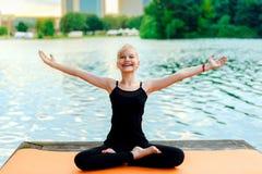 Счастливый ребенок приниманнсяая за йога на речном береге стоковые изображения