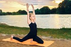 Счастливый ребенок приниманнсяая за йога на речном береге стоковое изображение rf