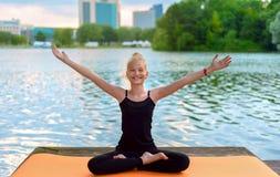 Счастливый ребенок приниманнсяая за йога на речном береге стоковое фото rf