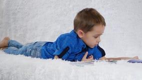 Счастливый ребенок счастливо читает книгу лежа на белой софе r сток-видео