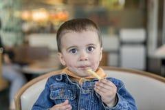 Счастливый ребёнок ест французские фраи Быстро-приготовленное питание европейско стоковое фото