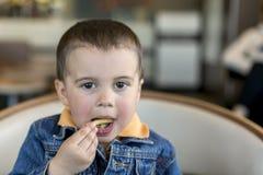 Счастливый ребёнок ест французские фраи Быстро-приготовленное питание европейско мальчик 2 года старого конца-вверх есть французо стоковая фотография
