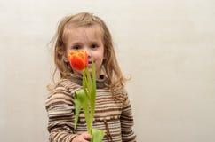 Счастливый ребёнок радуется и усмехается с букетом пестротканых тюльпанов в руках Стоковое фото RF