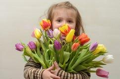 Счастливый ребёнок радуется и усмехается с букетом пестротканых тюльпанов в руках Стоковая Фотография