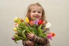 Счастливый ребёнок радуется и усмехается с букетом пестротканых тюльпанов в руках Стоковые Фотографии RF