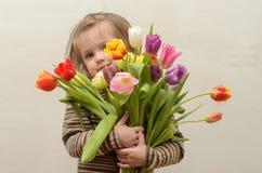 Счастливый ребёнок радуется и усмехается с букетом пестротканых тюльпанов в руках Стоковые Изображения