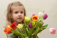 Счастливый ребёнок радуется и усмехается с букетом пестротканых тюльпанов в руках Стоковое Изображение