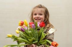 Счастливый ребёнок радуется и усмехается с букетом пестротканых тюльпанов в руках Стоковое Фото