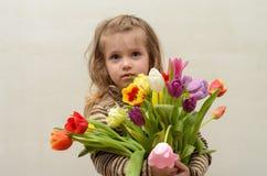 Счастливый ребёнок радуется и усмехается с букетом пестротканых тюльпанов в руках Стоковое Изображение RF