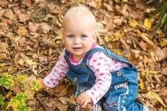Счастливый ребёнок смеясь над и играя в осени на лесе Стоковые Фотографии RF