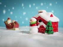 Счастливый Санта Клаус с коробкой подарков на скелетоне снега идя идти снег дом около дома снега имейте снеговик и рождественскую Стоковое фото RF