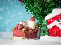 Счастливый Санта Клаус с коробкой подарков на скелетоне снега идя расквартировать около дома имейте снеговик и рождественскую елк Стоковые Фото