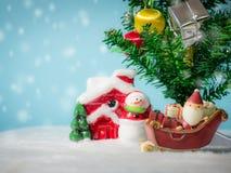 Счастливый Санта Клаус с коробкой подарков на скелетоне снега идя расквартировать около дома имейте снеговик и рождественскую елк Стоковые Изображения