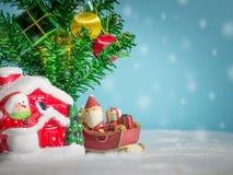 Счастливый Санта Клаус с коробкой подарков на скелетоне снега идя расквартировать около дома имейте снеговик и рождественскую елк Стоковая Фотография RF