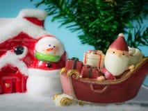 Счастливый Санта Клаус с коробкой подарков на скелетоне снега идя расквартировать около дома имейте снеговик и рождественскую елк Стоковые Фотографии RF