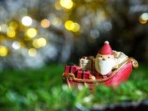 Счастливый Санта Клаус с коробкой подарков на скелетоне снега идя расквартировать около дома имейте снеговик и рождественскую елк Стоковое Изображение RF