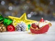 Счастливый Санта Клаус с коробкой подарков на скелетоне снега идя расквартировать около дома имейте снеговик и рождественскую елк Стоковое Фото