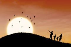 Счастливый силуэт семьи с ландшафтом захода солнца Стоковые Фотографии RF