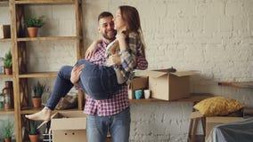 Счастливый сильный человек завихряет его жену и целует ее во время перестановки к новому дому после покупать его романтично видеоматериал