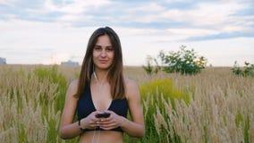 Счастливый смартфон и наушники пользы молодой женщины идя в поле на заходе солнца, здоровом образе жизни Использование бегуна Spo видеоматериал