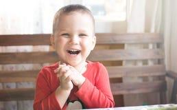 Счастливый смех мальчика смотря портрет камеры стоковая фотография