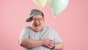 Счастливый смешной человек очень подобный Winnie the Pooh с baloons воздуха изолированными над розовой предпосылкой акции видеоматериалы