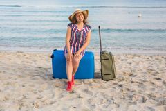 Счастливый смеясь над турист женщины при чемоданы сидя около моря Концепции перемещения и летних каникулов Стоковые Изображения