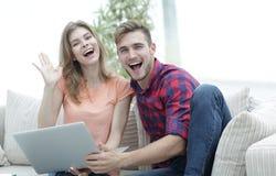 Счастливый смеяться над пар, сидя на кресле перед открытой компьтер-книжкой Стоковая Фотография RF